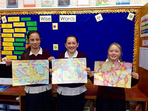 Tyra, Mia, and Maddie show some of their completed