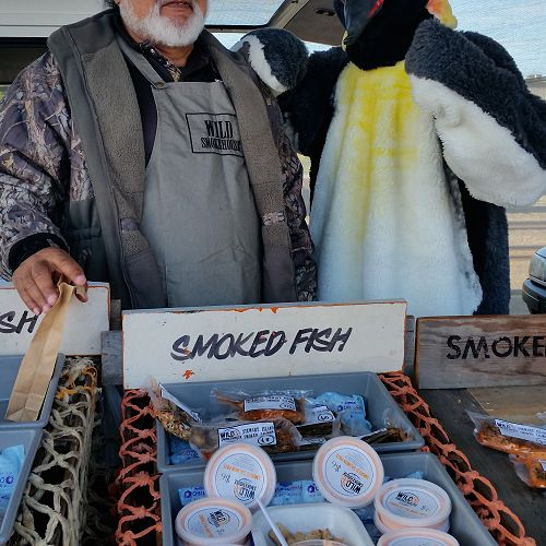 Joseph Ruka from Wild Smokehouse not too sure about having Jack our penguin so close to his smoked fish products.