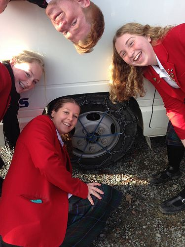 OED students fit chains to the school bus