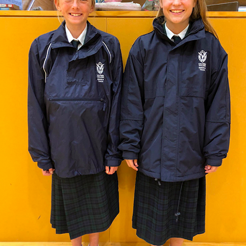 Rachel Turner (left) wearing the navy blue pull over water proof lightweight rain jacket and Jorja Dinan (right) wearing the navy blue zip-up fleece-lined jacket