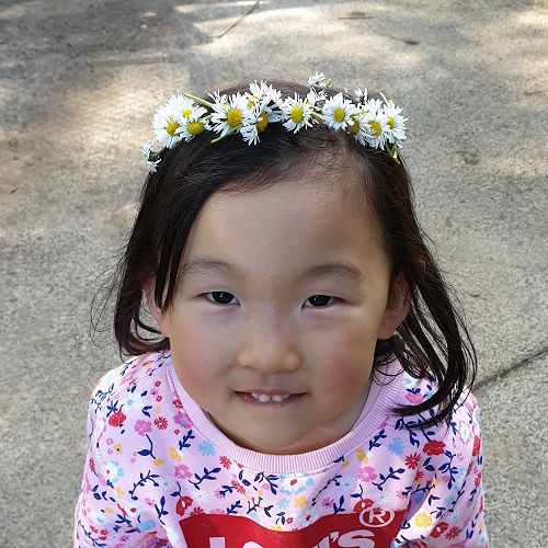 Shania from Room 18 with her lovely Daisy Chain Crown made from the daisies on the big field