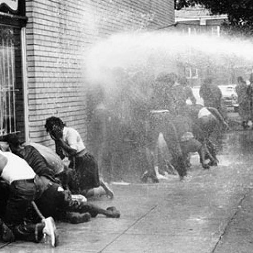 Citizens of Birmingham, Alabama are forced into submission by police with fire hoses, 1950s.