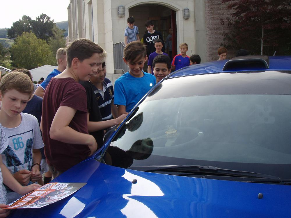 Year 7 and 8 students admire one of the rally cars that will race this weekend