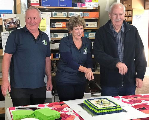 Gerard and Barbara prepare to cut the cake with company founder, Ross King