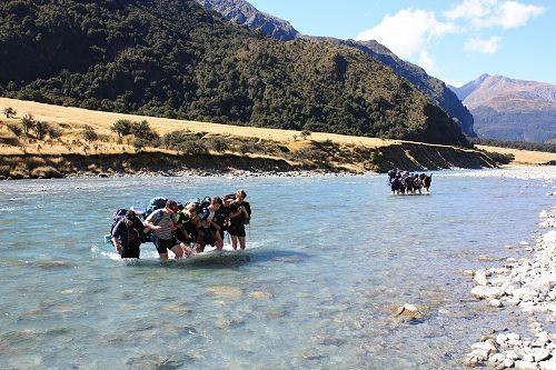 Two groups crossing the Matukituki river on the wa