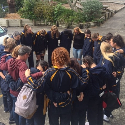 Basketball girls leaving for their first game, being prayed for by the Netball girls