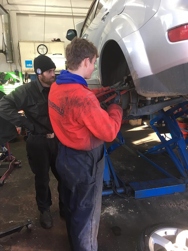 Archie Calder replaces brake pads at Automotive Solutions under the watchful eye of his mentor