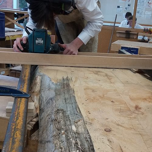 Michael Beattie using the jig he created to level out a 100 year slab of Macrocarpa.