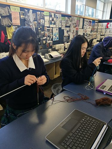 Abby Poon and Ella Xu concentrate on their knitting.
