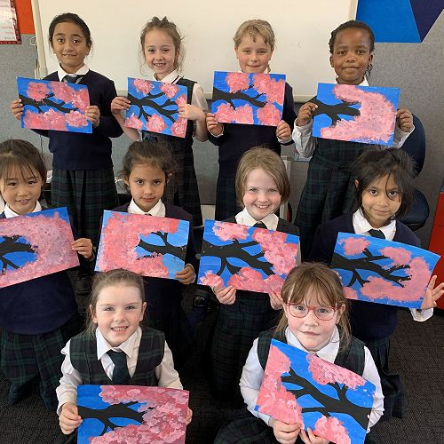 Year 2-3 students proudly showing their artwork.