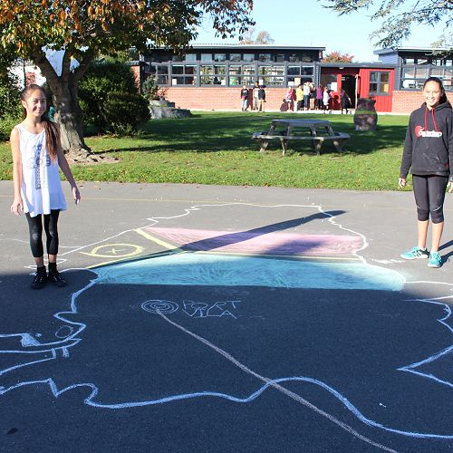 Anika and Amy-Lee with their chalk drawn Vanuatu.