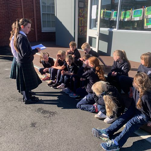 Ruby Acklin explains to Year 3 and 4 children how the 'Gratitude Scavenger Hunt' will work.