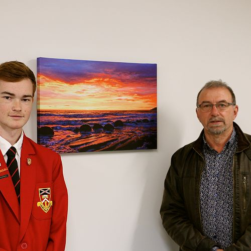 Ethan Hornsby and Mr Hayward pictured with Ethan's Canvas of Moeraki Boulders