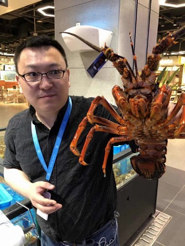 Hema's Shanghai Purchasing Director, Mr Wan<br /> holds up one of our branded lobsters at the opening of the flagship store in<br /> Hangzhou