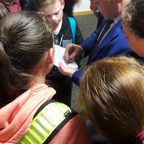 Waimakariri MP Matt Doocey signs the school books of students from Casebrook Intermediate.