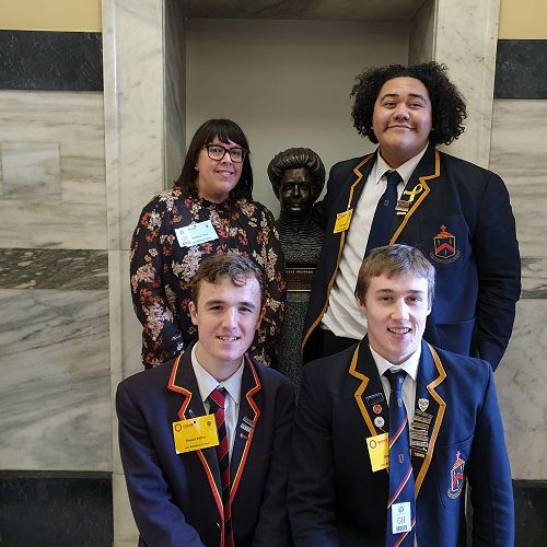 Ms Fridd, Ezekiel, Stewart, and Ben pose with Kate Sheppard in Parliament. They've recently finished a devising unit on Women's Suffrage.