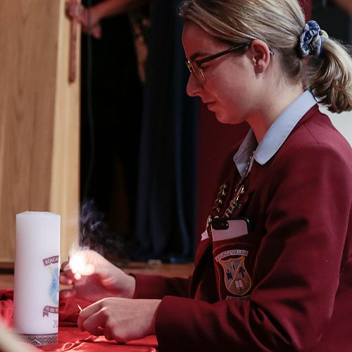 Briana Grace lighting the College candle at the beginning of the Holy Thursday Liturgy