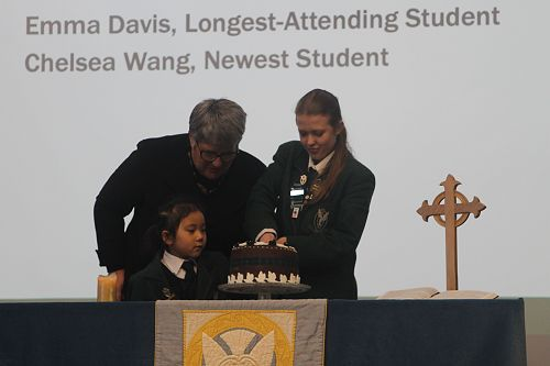 Mrs Duthie, Emma Davis and Chelsea Wang cut the Saint Columba Day cake