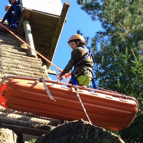 Cory and the boys from Gilray House lower Jacob down the abseiling wall in a stretcher