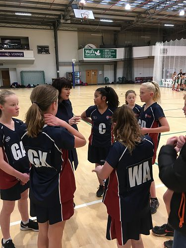 Coach Rachel Mortimer gives some sound advice during halftime in the year 7 Gold netball game at the junior catholic schools tournament.