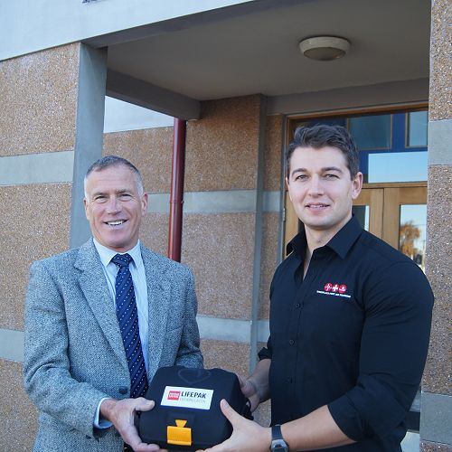 Mr Ross (left) receives the Automated External Defibrillator (AED) from Old Boy Craig Newton (2001-2005).