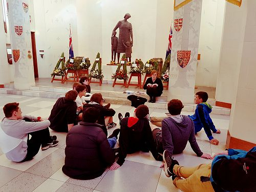 Ashley speaking to the students in the Hall of Memories about the ceremony. Wreaths laid by various dignitaries are visible in the back.
