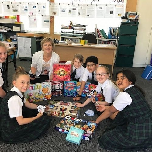 Year 6 students with Mrs Hutton enjoying a selection of their new class board games.