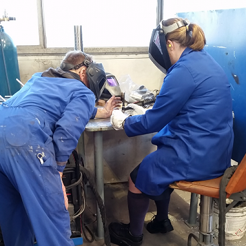 Christiana O'Connor learning to TIG weld at Hamilton Jet Marine Division with Colin overseeing the process.