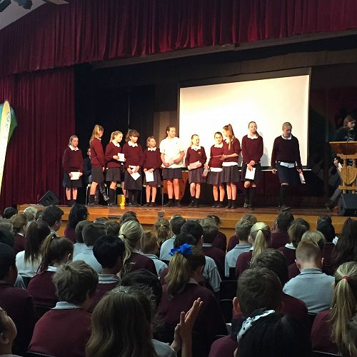 The girls on stage during assembly receiving their 1st place certificates for the season.
