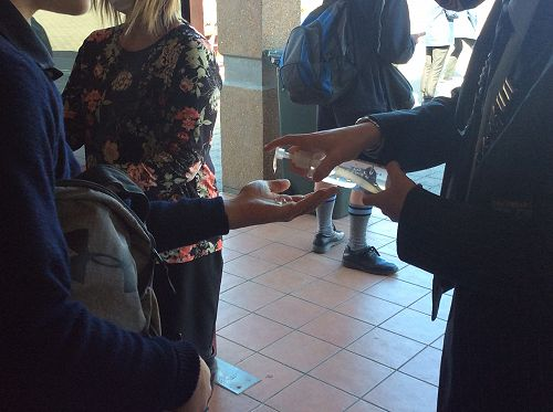 Hands being sanitized after each students has voted