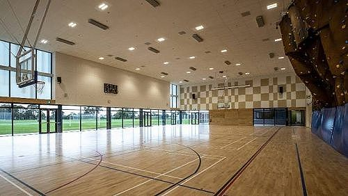 Gym with climbing wall and sports fields in the distance