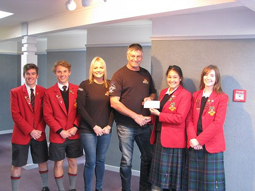 Head students hand over a cheque for $500 to Chris