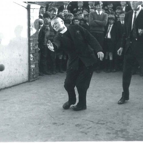 Father Durning (First XV Coach) and D. O'Brien (manager of the British Lions team) playing Five Court. Father Durning throws the ball as O'Brien stands to his side ready to hit it back. Students stand behind to watch the game.