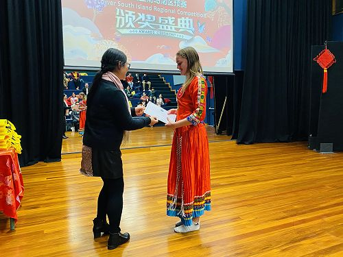 Charli Sinclair receiving her prize from Prof Yu