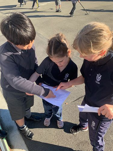 Peter Choi helps Maya Marra and Maia Hayden to read through their list.