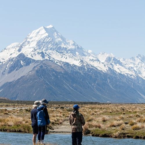 Jin Kim fishes for the elusive Monster trout with Aoraki Mt Cook in the background (and a group of supporters).
