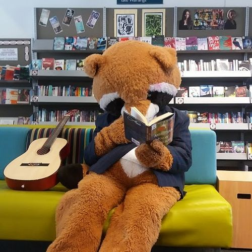 School Mascot, Riccy the Racoon, checking out one of the books from RHS Book Club.