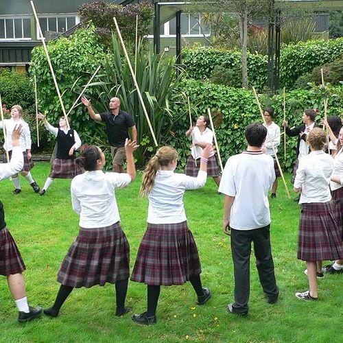 Matua Tip and students using rakau